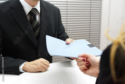 Employment interview with female applicant handing over a file c