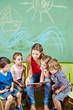 Erzieher und Kinder lesen Buch im Kindergarten