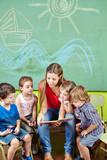 Fototapety Erzieher und Kinder lesen Buch im Kindergarten
