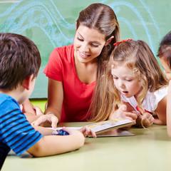 Erzieher im Kindergarten und Kinder lesen Buch