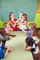 Kinder spielen mit Regenmacher im Kindergarten