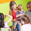 Kindergärtnerin und Kinder lesen gemeinsam Buch
