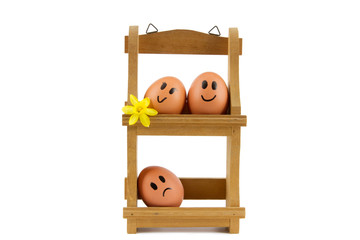 wooden egg rack with three eggs with facial expressions