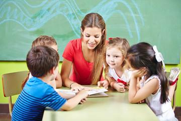 Erzieherin und Kinder lesen Buch in Kita