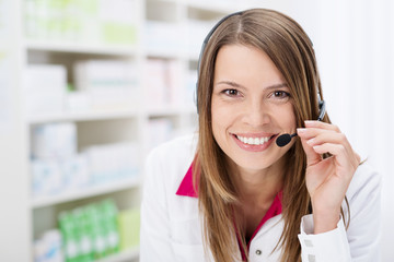 lächelnde apothekerin telefoniert mit headset