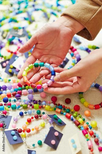 Hände halten bunten Schmuck beim Juwelier
