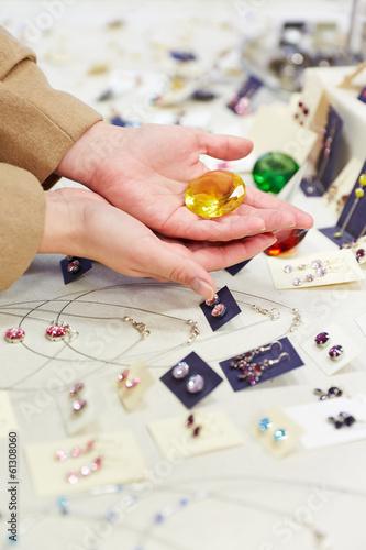 Hände halten Schmuckstein beim Juwelier