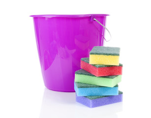 Pile of colorful sponge scourer and pink bucket over white backg