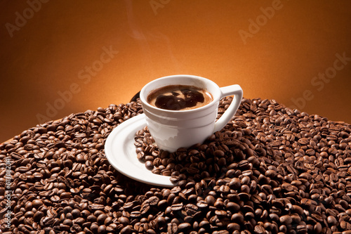 Cup of coffee and coffee beans on the background of Terracotta