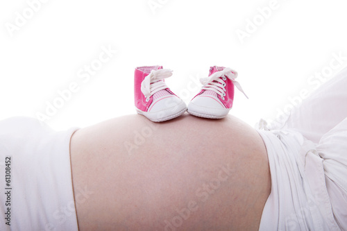 Little pink shoes on pregnant belly