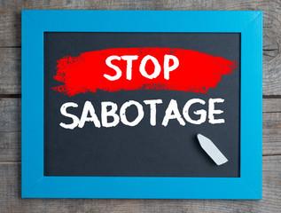 Stop sabotage on blackboard on wooden table