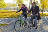 Young couple riding a bicycle in autumn park
