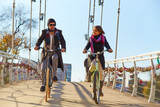 Young couple riding a bicycle across the bridge