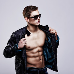 Young handsome macho man in sunglasses with open leather jacket