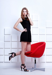 beautiful young woman in short black dress and black shoes