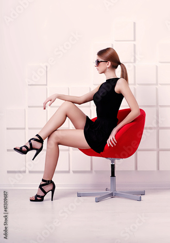 Sexy woman sitting on a chair. Fashion shot