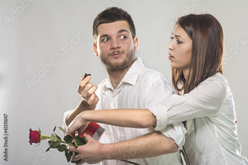 Young man teasing his girlfriend with candies