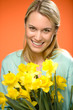 Smiling woman hold yellow narcissus spring flowers