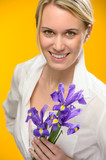 Woman hold one spring iris flower smiling