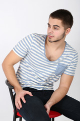 Handsome young man sitting on chair on light background