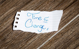 Time for change written on the paper on a wood background
