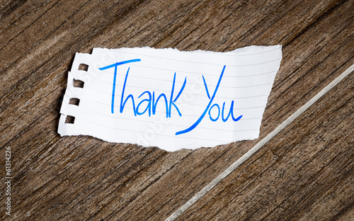 Thank You handwriting note on a wooden background