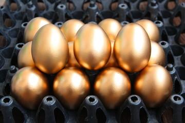 Golden eggs on black package