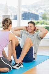Trainer assisting fit man in doing sits up