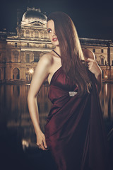 Beautiful fashion model poses with Louvre museum in background