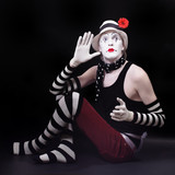 Mime in white hat with red flower sits on the floor