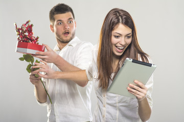 Young woman rejecting gifts from her boyfriend except tablet