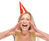 Happy woman in party cap shouting through megaphone shaped hands