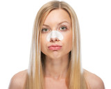 Concerned young woman with clear-up strips on nose