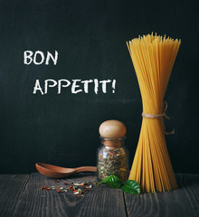 spaghetti and spices on blackboard background. bon appetit text