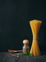 spaghetti and spices on blackboard background. copy space