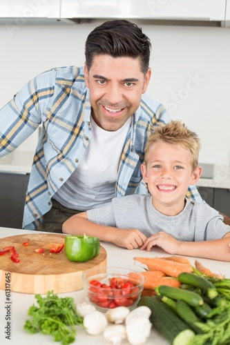 Smiling father showing his son how to prepare vegetables