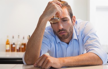 Drunk businessman clutching whiskey glass to head