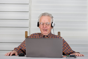 Old man with headphones and laptop feeling frustrated