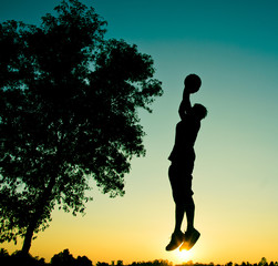Player and basketball silhouette sunset background