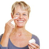 Elderly woman putting skin care lotion on face