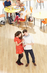 Overhead Shot Of Student Couple Standing In Cafeteria
