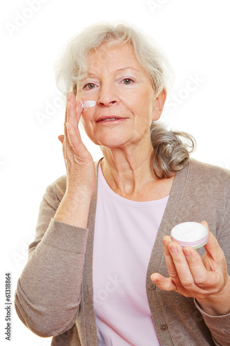 Senior woman putting lotion on her face