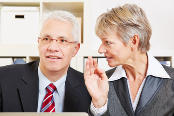 Business woman whispering secret in man's ear
