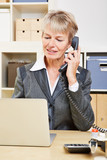 Elderly business woman in office making phone call