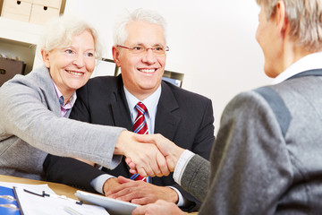 Elderly couple shaking hands with legal consultant