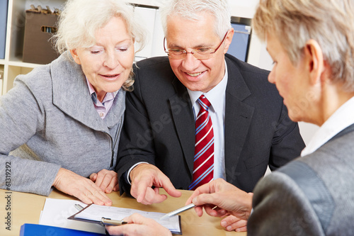 Senior couple writing signature under contract