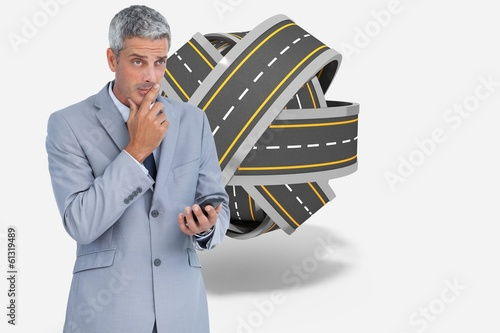 Composite image of worried businessman holding his cellphone