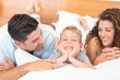 Cute young family lying on bed together smiling