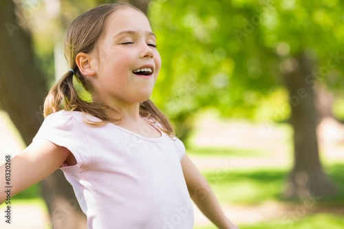Girl with arms outstretched and eyes closed at park