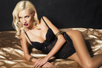 sexy blond woman in lingerie lying on the gold material